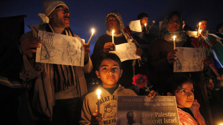 Palestinians light candles as hold pictures of late South African leader Nelson Mandela, during an honor ceremony at the Unknown Soldier Square in Gaza City, Sunday, Dec. 8, 2013. Palestinians mourned Mandela as a loyal champion of their cause. Palestinian and South Africa flags are seen. (AP Photo/Adel Hana)
