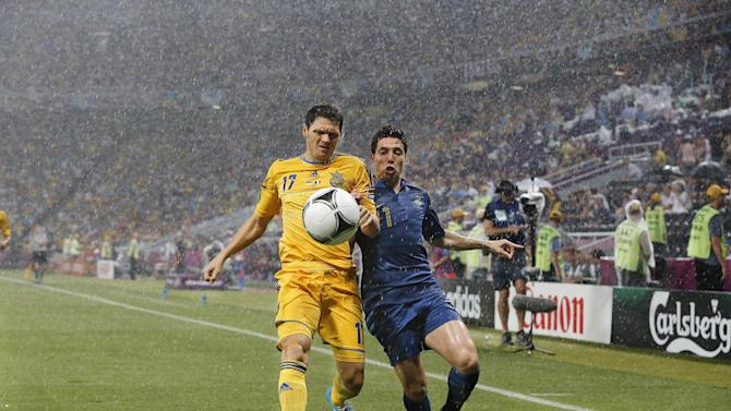 Ukraine's Taras Mikhalik, left, and France's Samir Nasri fight for the ball during the Euro 2012 soccer championship Group D match between Ukraine and France in Donetsk, Ukraine, Friday, June 15, 2012. The match was suspended because of a thunderstorm.(AP Photo/Matthias Schrader)