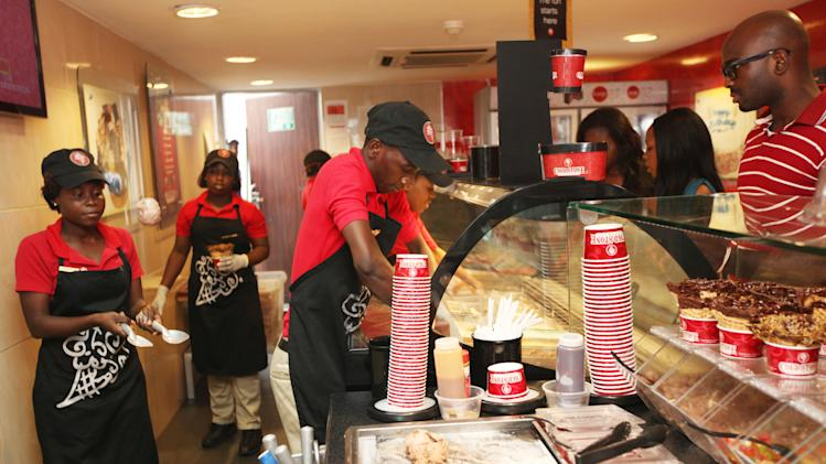 In this photo taken, Sunday, Feb. 10, 2013 customers wait to buy Cold Stone ice cream in Lagos, Nigeria. As Nigeria's middle class grows along with the appetite for foreign brands in Africa's most populous nation, more foreign restaurants and lifestyle companies are entering the country. And the draw on Nigerians' new discretionary spending has also put new expectations on providing quality service in a nation where many have grown accustomed to expecting very little. ( AP Photo/Sunday Alamba)