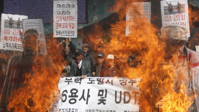 "South Korean conservative activists burn cutout pictures of North Korean national founder the late Kim Il Sung, right, and late leader Kim Jong Il during a rally to mark the third anniversary of the sinking of South Korean naval ship ""Cheonan"" which killed 46 South Korean sailors, in Seoul, South Korea, Tuesday, March 26, 2013. An explosion ripped apart the 1,200-ton warship, killing 46 sailors near the maritime border with North Korea in 2010.  A banner reads: ""Bomb at statue of Kim Jong Il and Kim Il Sung."" (AP Photo/Ahn Young-joon)"