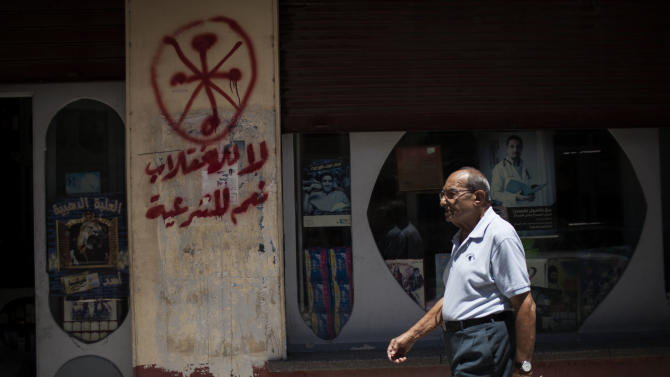 "An Egyptian man walks in front of a pharmacy marked with anti-Coptic and anti-coup graffiti in Assiut, Upper Egypt, Tuesday, Aug. 6, 2013. Islamists may be on the defensive in Cairo, but in Egypt's deep south they still have much sway and audacity: over the past week, they have stepped up a hate campaign against the area's Christians. Blaming the broader Coptic community for the July 3 coup that removed Islamist President Mohammed Morsi, Islamists have marked Christian homes, stores and churches with crosses and threatening graffiti. Arabic grafitti reads, ""No to the coup and yes to legitimacy."" (AP Photo/Manu Brabo)"