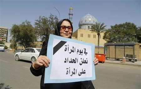 "Iraqi woman holds sign during a demonstration against the draft of the ""Al-Jafaari"" Personal Status Law during International Women's Day in Baghdad"