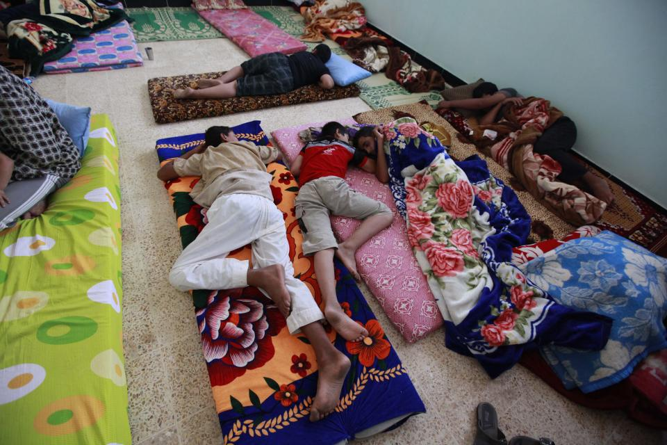 Syrian refugees rest as they have crossed  the border by the Iraqi town of Qaim, 200 miles (320 kilometers) west of Baghdad, Iraq, Tuesday, Aug. 7, 2012. (AP Photo/Hadi Mizban)