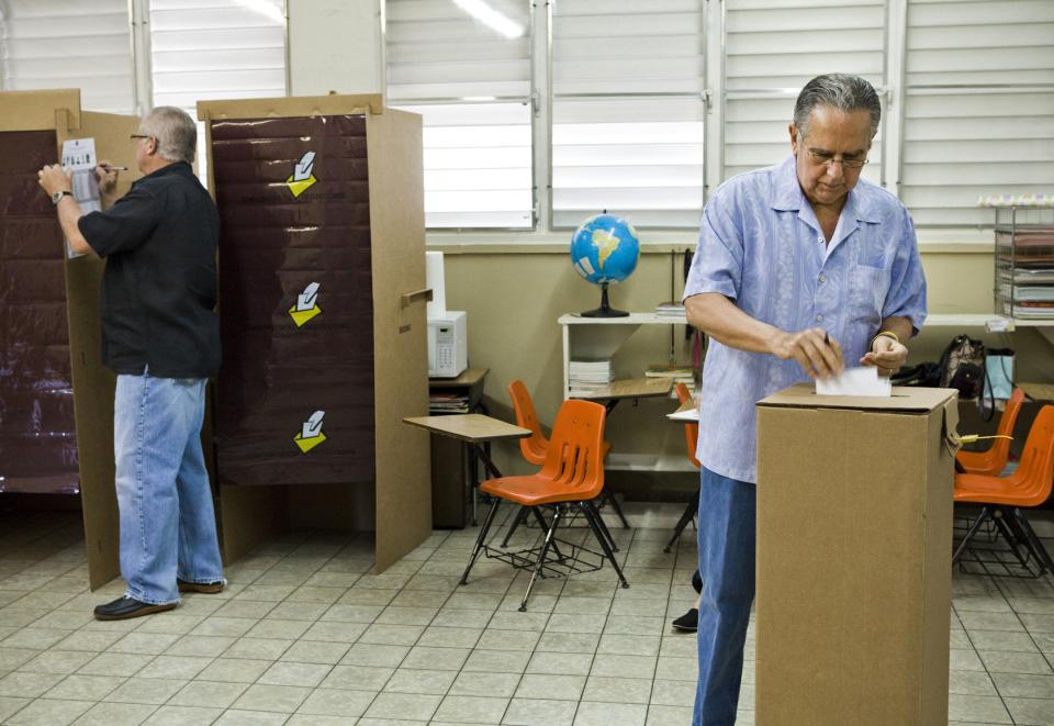 Fred Martinez, right, and Alfonso Lozada vote in the Republican presidential primary election at San Jose Academy in Guaynabo, Puerto Rico, Sunday March 18, 2012.  Puerto Rico's residents cannot vote in general elections, but are set to award 20 delegates in their Sunday Republican primary.  (AP Photo/Christopher Gregory)