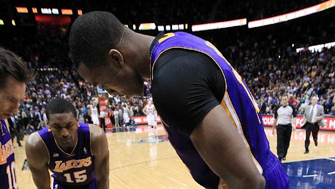 Los Angeles Lakers' Dwight Howard leans over teammate Kobe Bryant lays on the floor after being injured in the final seconds of an NBA basketball game against the Atlanta Hawks on Wednesday, March 13, 2013, in Atlanta. The Hawks defeated the Lakers 96-92.  (AP Photo/Atlanta Journal-Constitution, Curtis Compton)