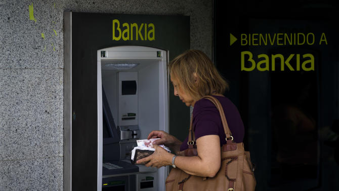 A woman uses an ATM cash point machine at a branch of the Bankia bank in Madrid, Wednesday, June 6, 2012. The Spanish economy is in recession for the second time in three years as the damage from a housing bust persists. Foreclosures are rising, Spain's banks are in worse financial shape and the government's deficit is hitting worrisome levels. The impact of the budget cuts has been brutal and unemployment has swelled to nearly 25 percent. Among people under age 25 it is a staggering 52 percent . (AP Photo/Daniel Ochoa de Olza)