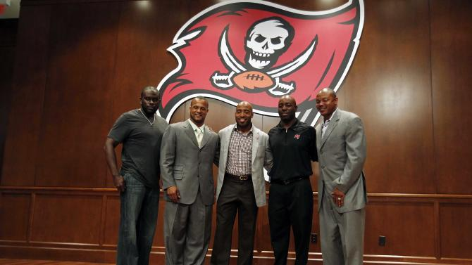 May 9, 2013; Tampa, FL, USA; Tampa Bay Buccaneers cornerback Ronde Barber (middle) poses with former teammates during his retirement press conference at One Buccaneer Place. (Kim Klement-USA TODAY Sports)