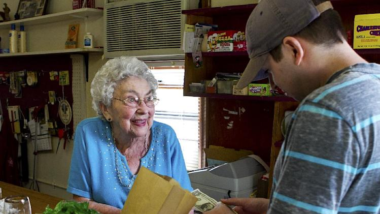 Matt Pilz buys candy from Marge Wolf, 96, at Wolf's Groceries in Marshfield, Wisc., Tuesday, July 16, 2013, the day after an attempted robbery at knifepoint happened at her store. The masked man ordered Wolf to open the cash register. She told him he could have all the Tootsie Rolls he wanted, but she wasn't going to open the register, and stood her ground when the would-be robber flashed his knife. The frustrated robber spotted a security camera in the corner, decided it wasn't worth it and fled on foot. (AP Photo/News-Herald, Megan Mccormick)