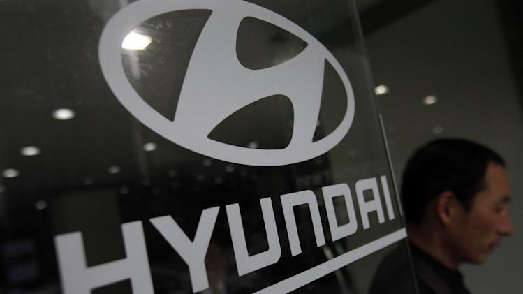 Visitor walks past a Hyundai Motor logo at a Hyundai dealership in Seoul