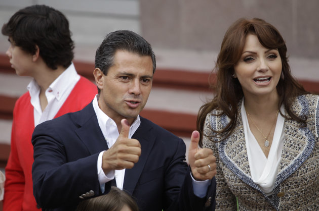 Enrique Pena Nieto, presidential candidate for the Revolutionary Institutional Party (PRI), accompanied by his wife Angelica Rivera, flashes his election ink-stained thumbs after he cast his vote in t