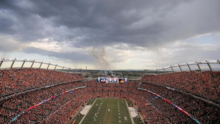 Storm clouds gather as fireworks are launched prior to an NFL football game between the Baltimore Ravens and the Denver Broncos, Thursday, Sept. 5, 2013, in Denver. (AP Photo/Brennan Linsley)
