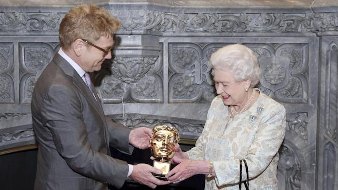 """Queen Elizabeth II receives an honorary British Academy award (Bafta) Thursday April 4 2013,  at Windsor Castle, west of London, from  actor and director Kenneth Branagh, in recognition of her lifetime's support of British film and television - and for being the most """"memorable Bond girl yet"""", in her London Olympics opening role. (AP Photo/Steve Parsons, pool)"""