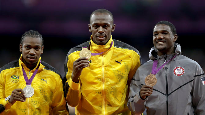 Jamaica's Usain Bolt, center, poses with his gold medal for the men's 100-meters with compatriot and silver medalist Yohan Blake, left, and United States' Justin Gatlin, bronze, right, during the athletics in the Olympic Stadium at the 2012 Summer Olympics, London, Monday, Aug. 6, 2012. (AP Photo/Matt Slocum)