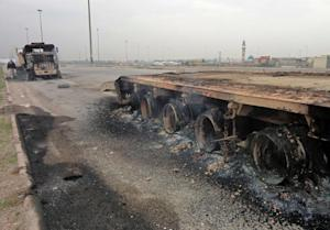 Burnt-out lorries are seen littering the side of the …