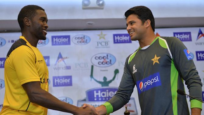 Pakistani cricket captain Azhar Ali (R) shakes hands with his Zimbabwe counterpart Elton Chigumbura after the unveiling of the One Day International trophy in Lahore on May 25, 2015