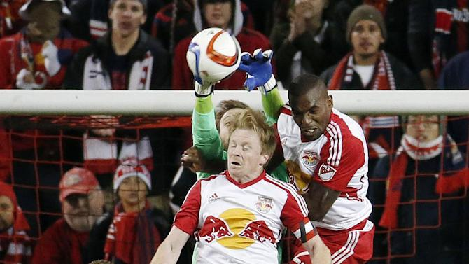 Columbus Crew goalkeeper Steve Clark, back, clears the ball as New York Red Bulls' Dax McCarty, center, and Ronald Zubar, right, go up for the challenge during the second half of the second leg of the MLS soccer Eastern Conference championship, Sunday, Nov. 29, 2015, in Harrison, N.J. (AP Photo/Julio Cortez)