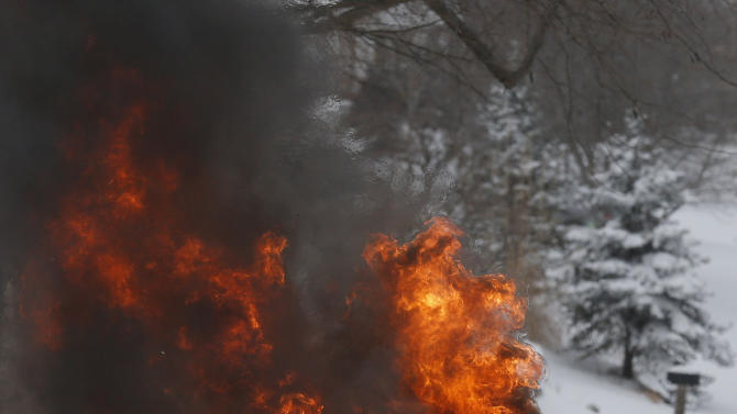 A Lawrence Firefighter prepares to extinguish a vehicle fire in Lawrence, Kan., Thursday, Feb. 21, 2013. The car caught on fire trying to make it up a snow covered hill on Lawrence Avenue. (AP Photo/Orlin Wagner)