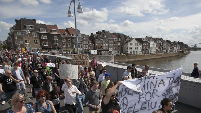 """Demonstrators carry a banner reading """"no discrimination for Belgium"""" during a protest rally against the new marijuana buying policy in Maastricht, southern Netherlands, Tuesday May 1, 2012. A policy barring foreign tourists from buying marijuana in the Netherlands goes into effect in parts of the country Tuesday, with a protest planned in the southern city of Maastricht. Weed is technically illegal in the Netherlands, but it is sold openly in small amounts in designated cafes under the country's famed tolerance policy. The government has said that as of May 1, only holders of a """"weed pass"""" will be allowed to purchase the drug, and nonresidents aren't eligible. (AP Photo/Peter Dejong)"""