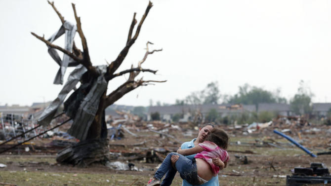 A woman carries a child through a field near the collapsed Plaza Towers Elementary School in Moore, Okla., Monday, May 20, 2013.  A tornado as much as a mile wide with winds up to 200 mph roared through the Oklahoma City suburbs Monday, flattening entire neighborhoods, setting buildings on fire and landing a direct blow on an elementary school. (AP Photo Sue Ogrocki)