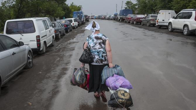 A woman carries her belongings heading to the Ukrainian-Russian border checkpoint in Izvaryne as she leaves Ukraine, Friday, June 20, 2014. Some Ukrainians are leaving amid fighting in eastern Ukraine. Clashes between government forces and pro-Russia rebels flared ahead of the publication of a presidential peace plan that includes a unilateral cease-fire. (AP Photo/Evgeniy Maloletka)