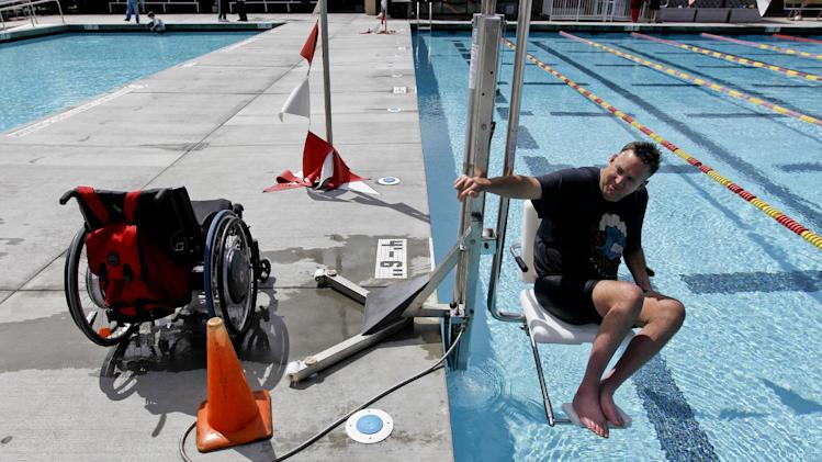 In this April 11, 2012 photo, Stefan Freeman demonstrates how to access a swimming pool using a hydraulic car lift in Mission Viejo, Calif. Hotels, municipal recreation centers and other swimming pool operators are scrambling to comply with new government regulations requiring public pools to be accessible to people with disabilities. (AP Photo/Chris Carlson)
