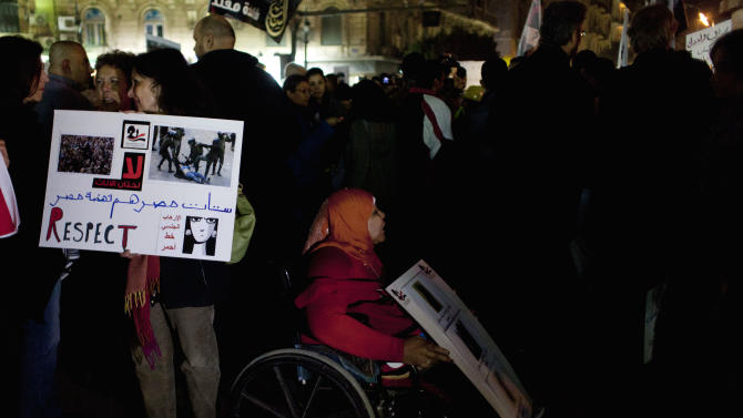 "Egyptian women activists, one on a wheelchair, take part in a protest for women against sexual harassment and against theIslamist dominated Shura Council blaming women for the attacks against them, in Cairo, Egypt, Tuesday, Feb. 12, 2013. Arabic on the placard reads ""Egyptian women are Egypt's development. Respect"" (AP Photo/Nasser Nasser)"