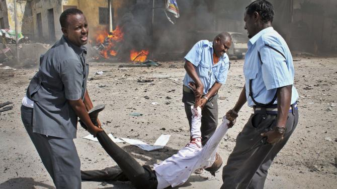 EDS NOTE: GRAPHIC CONTENT - Somali security force members carry away a severely wounded man following a suicide car bomb blast in the capital Mogadishu, Somalia Sunday, May 5, 2013. A Somali police official at the scene said four civilians and a soldier were killed after the bomber attempted to ram a car laden with explosives into a military convoy. (AP Photo/Farah Abdi Warsameh)