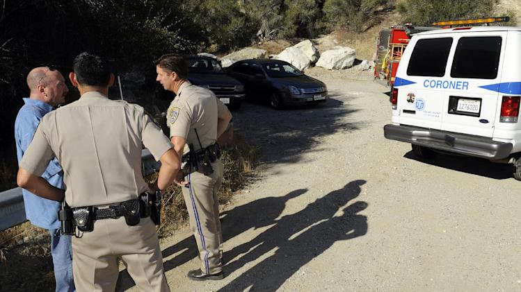 California Highway patrol officers investigate the scene of two cars that were recovered at the bottom of a remote mountain  in Castaic, Calif., Friday, Sept. 30, 2011 .  David Lavau, whose car had plunged 200 feet off a remote mountain road, was found yesterday by his three adult children, who had enlisted the help of a missing persons detective. Lavau suffered multiple rib fractures, a broken arm and multiple fractures in his back.  While he was being rescued, another vehicle was found nearby, its driver dead. Authorities don't know if that vehicle was involved in a collision with Lavau's car, or if it was a separate accident. (Photo/Gus Ruelas)