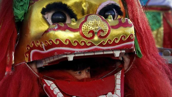A lion dance performer looks out from the mouth of the lion head at Ditan Park to mark the first day of Chinese Lunar New Year in Beijing, Monday, Feb. 8, 2016. Millions of Chinese began celebrating the Lunar New Year, which marks the Year of the Monkey on the Chinese zodiac. (AP Photo/Andy Wong)