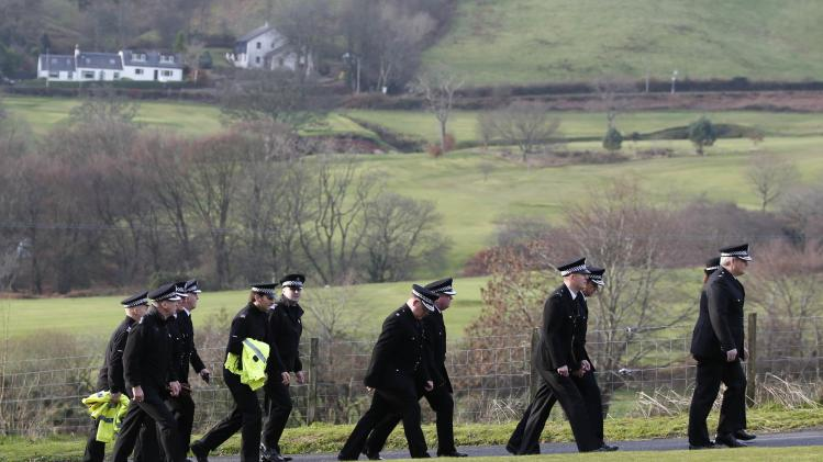 Police officers walk through Lamlash Cemetry for the funeral of police officer Tony Collins, Isle of Arran, Scotland