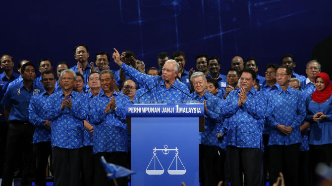 In this Saturday, April 6, 2013 photo, Malaysian Prime Minister Najib Razak, center, speaks during the launch of his ruling National Front coalition's manifesto for the upcoming general elections in Kuala Lumpur, Malaysia. With less than a week to general elections, Malaysia's opposition alliance is banking on the promise of bold change to end the governing coalition's 56-year rule. It says a new economic playing field will strip away decades of race-based policies that it believes bred corruption and hampered growth. (AP Photo/Lai Seng Sin)