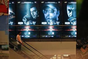 """A man rides an escalator past posters of the movie """"Waar"""" in Karachi"""