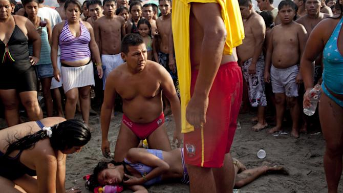 """In this March 3, 2013 photo, life guards attend Belen Godinez on""""Agua Dulce"""" beach after she was saved from drowning in the ocean in Lima, Peru. While Lima's elite spends its summer weekends in gate beach enclaves south of the Peruvian capital, the working class jams by the thousands on a single municipal beach of grayish-brown sands and gentle waves. The only barrier to entry to """"Agua Dulce"""" beach is two dollars, the price of bus fare to get there and home. (AP Photo/Rodrigo Abd)"""