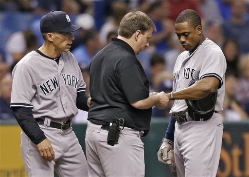 New York Yankees manager Joe Girardi, left, and a trainer, center, check Curtis Granderson's wrist during the fifth inning of a baseball game against the Tampa Bay Rays, Friday, May 24, 2013, in St. P