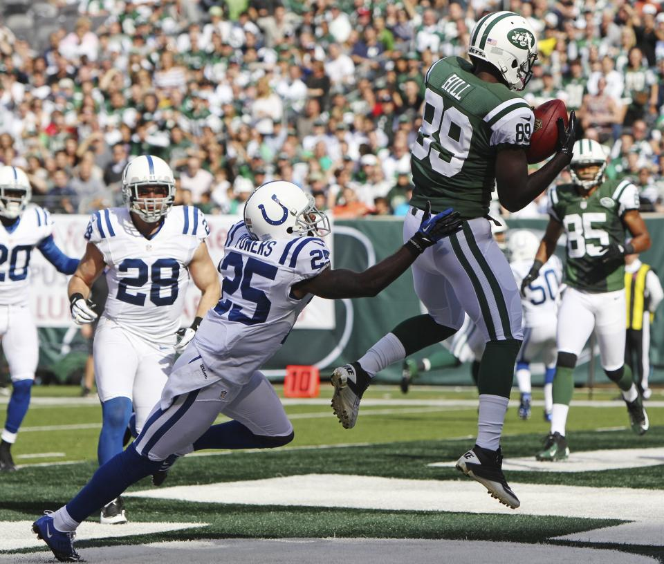 New York Jets wide receiver Jason Hill (89) catches a pass for a touchdown in front of Indianapolis Colts cornerback Jerraud Powers (25) during the first half of an NFL football game on Sunday, Oct. 14, 2012, in East Rutherford, N.J. (AP Photo/Seth Wenig)
