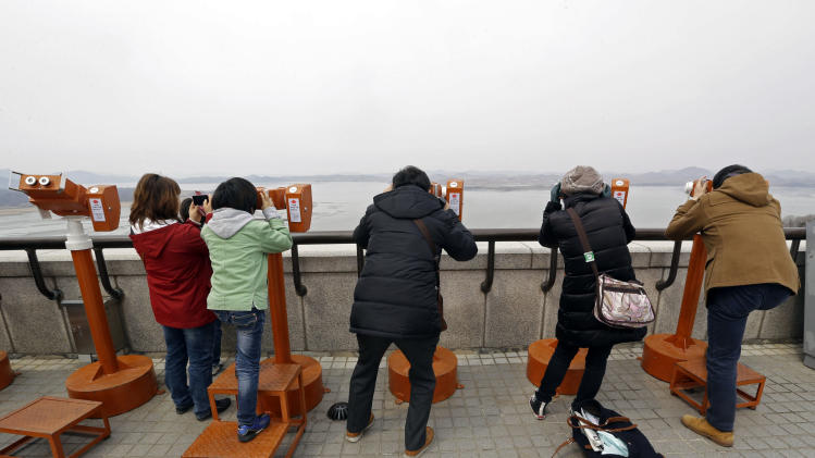"Visitors use binoculars to watch North Korean territory at the unification observation post near the border village of Panmunjom, that has separated the two Koreas since the Korean War, in Paju, north of Seoul, South Korea, Saturday, March 30, 2013. North Korea issued its latest belligerent threat Saturday, saying it has entered ""a state of war"" with South Korea a day after its young leader threatened the United States because two American B-2 bombers flew a training mission in South Korea. (AP Photo/Lee Jin-man)"