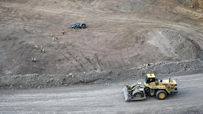Workers survey the base of the 500-foot-deep open pit at  Molycorp's Mountain Pass Rare Earth facility in Mountain Pass, California