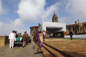 Military personnel carry the remains of the late Nelson Mandela upon arrival at the Union Buildings in Pretoria
