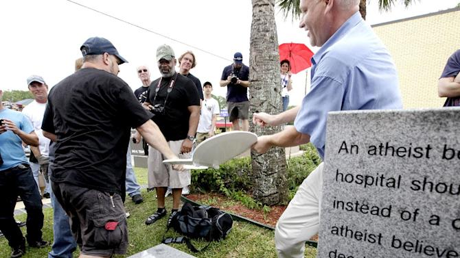 Sye Ten Bruggencate, with proofthatgodexists.org, has a toilet seat taken away from him as he tried to place it on the bench during the unveiling of an Atheist monument outside the Bradford County Courthouse on Saturday, June 29, 2013 in Stark, Fla. Bruggencate also tried to wrap the monument in toilet paper. The New Jersey-based group American Atheists unveiled the 1,500-bound granite bench Saturday as a counter to the religious monument in what's called a free speech zone. Group leaders say they believe it's the first such atheist monument on government property. About 200 people attended the event.(AP Photo/The Gainesville Sun, Matt Stamey)
