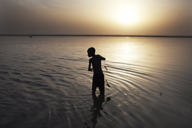 A boy casts a net for fish in the Niger River in Gao, Mali