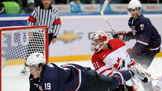 USA's Jake McCabe dives after taking a shot on Canada's goalie Jordan Binnington during their semi-final match at the the World Junior Ice Hockey championship in Ufa, Russia, Thursday, Jan. 3, 2013. (AP Photo/Yuri Kuzmin, KHL)