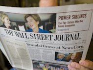 A person reads The Wall Street Journal in July 2011 in Washington, DC. Rupert Murdoch announced Thursday his News Corp conglomerate will press ahead with a split of the entertainment division from its struggling publishing business, saying he is committed to both units