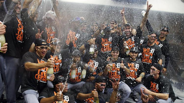 Detroit Tigers players celebrate amidst a rain of alcohol-free sparkling wine after they defeated the Minnesota Twins 1-0 in a baseball game, Wednesday, Sept. 25, 2013, in Minneapolis. The Tigers clinched the AL Central title. (AP Photo/Jim Mone)