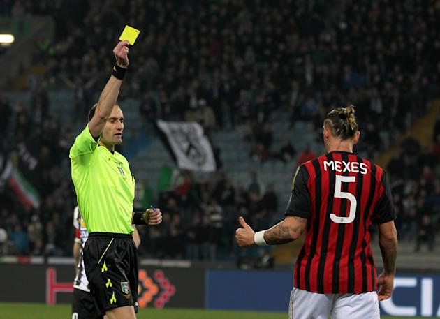 Referee Carmine Russo of Nola, shows a yellow card to AC Milan's Philippe Mexes during the Serie A soccer match between Udinese and AC Milan at the Friuli Stadium in Udine, Italy, Saturday, March