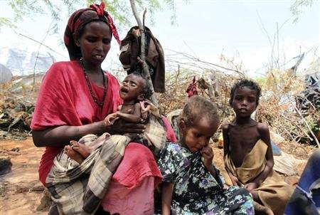 An internally displaced malnourished woman carries her child outside their makeshift shelter at a temporary camp in Hodan district of Somalia's capital Mogadishu August 26, 2011. REUTERS/Feisal Omar