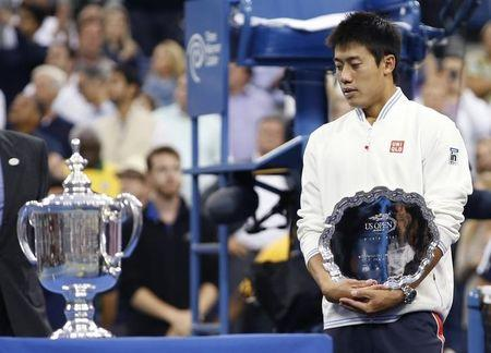 Nishikori of Japan holds his runner up trophy as he looks at the winner's trophy after being defeated in the men's singles final match by Cilic of Croatia at the 2014 U.S. Open tennis tournament in New York