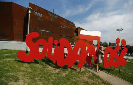 File photo of a woman standing next to a Solidarity logo in front of the newly open European Solidarity Centre during the 34th anniversary of emerging Solidarity trade union at the historic shipyard area in Gdansk