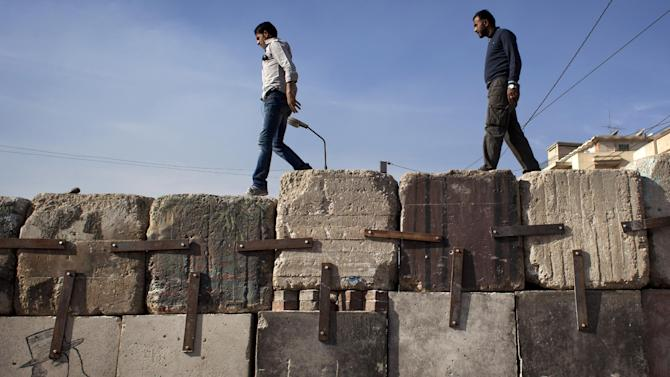 Two Egyptian protesters walk on top of cement blocks near the presidential palace, in Cairo, Egypt, Sunday, Dec. 9, 2012. Egypt's liberal opposition has called for more protests on Sunday after the president made concessions overnight that fell short of their demands to rescind a draft constitution going to a referendum on Dec. 15. (AP Photo/Nasser Nasser)
