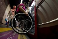 Brazilian Viviane Macedo, 35, gets in a metro car at a station in Rio de Janeiro. Challenges facing the disabled here run the gamut from subway elevators breaking down a lot, to sidewalks being uncommon, and often pocked with potholes