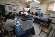 Election workers and ballot boxes are seen inside a polling station during a referendum on the new constitution in Cairo, January 15, 2014. REUTERS/Mohamed Abd El Ghany
